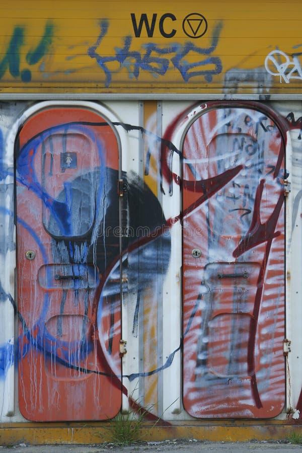 Grafittis em portas plásticas do toalete fotos de stock