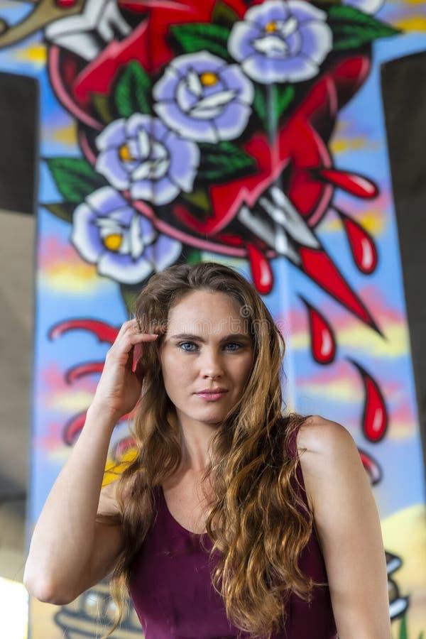 Grafittis morenos bonitos de Posing Outdoors Against do modelo fotos de stock royalty free