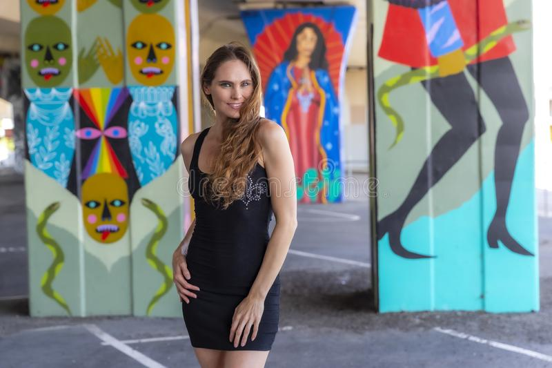 Grafittis morenos bonitos de Posing Outdoors Against do modelo fotografia de stock royalty free