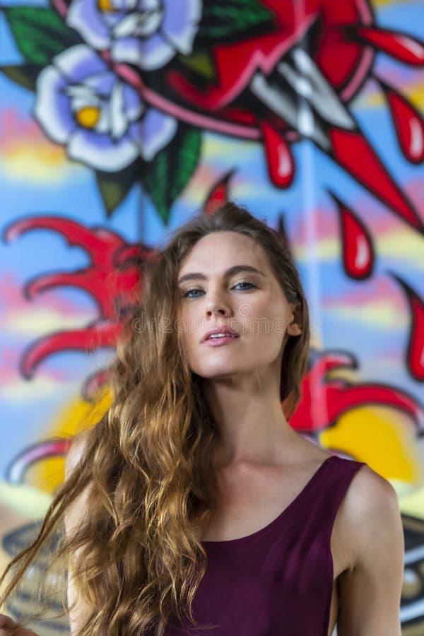 Grafittis morenos bonitos de Posing Outdoors Against do modelo foto de stock