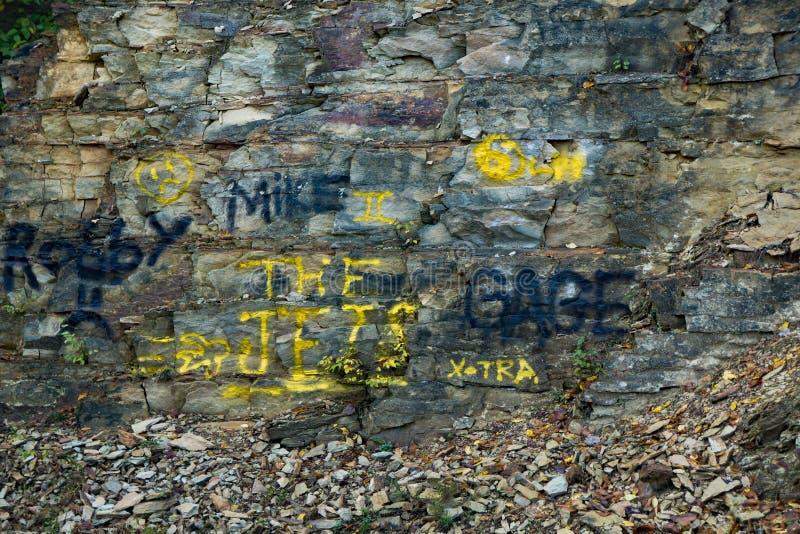 Grafittis pintados em uma parede da rocha imagem de stock royalty free