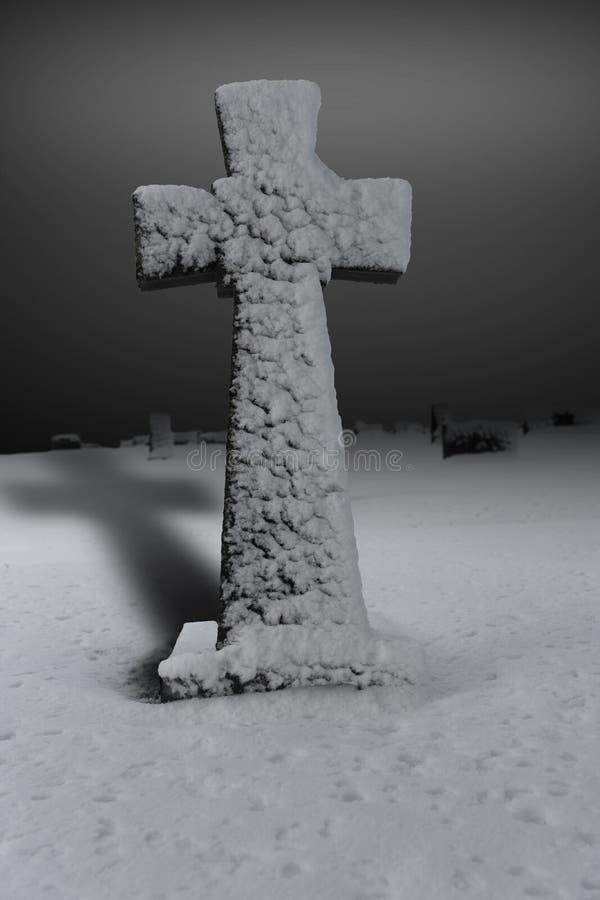Grafsteen in sneeuw wordt behandeld die stock afbeeldingen