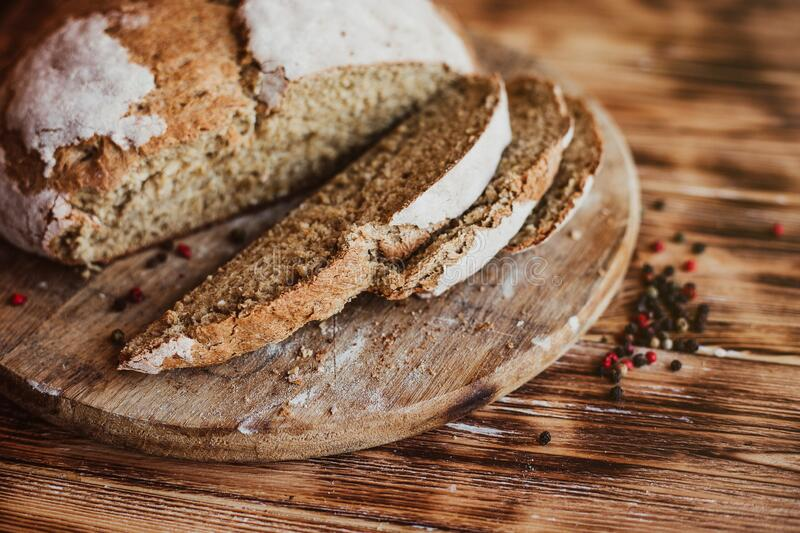Grain Artisan Bread Loaf. Rustic loaf of homemade bread sliced on dark wooden table. Homemade Loaf Of Bread. Selective focus stock photography