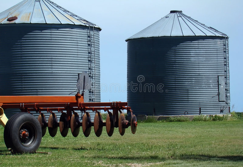 Grain Bins and Disc. Grain bins and partial view of disc cultivator on farm in Midwest royalty free stock images
