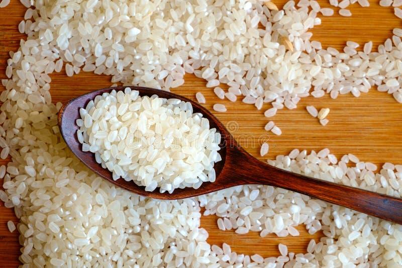 Grain de riz dans la cuillère en bois foncée photographie stock