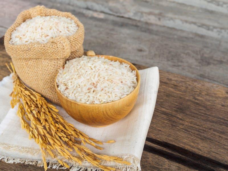 Grain de riz de jasmin sur la cuvette et le sac sur le vieux fond en bois photo libre de droits