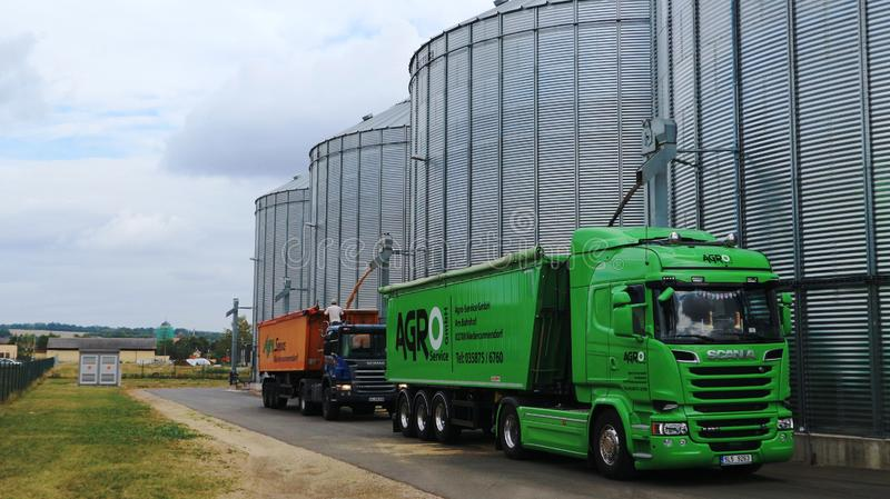 Grain from the elevator silo is loaded into the truck stock images