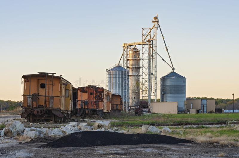 Grain Elevators and Abandoned Railcars. Grains elevators and rusty abandoned railcars on st feriole island in prairie du chien royalty free stock photo