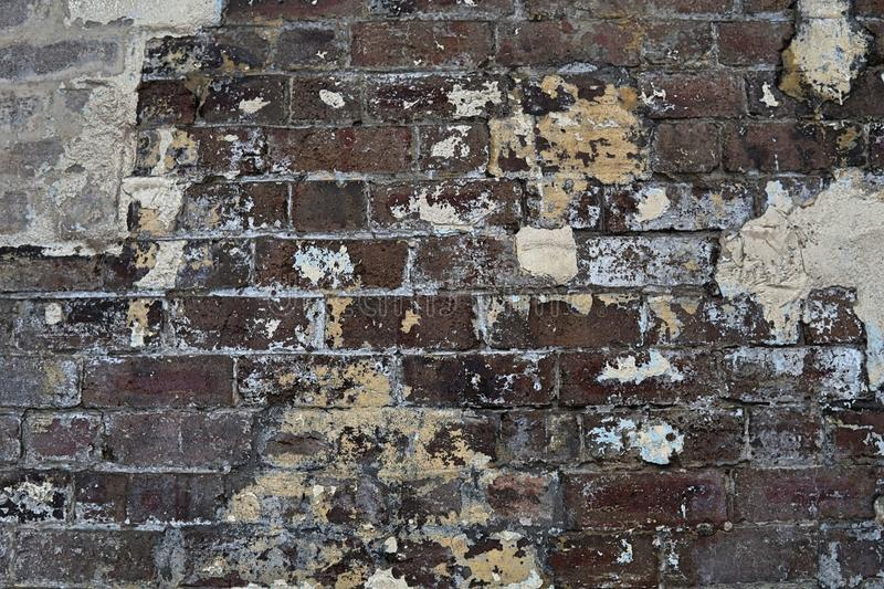 Grain Image of brick stone wall background in detail and texture patte. Rn. Dirty brick wall with peeling paint in abandon factory stock photography
