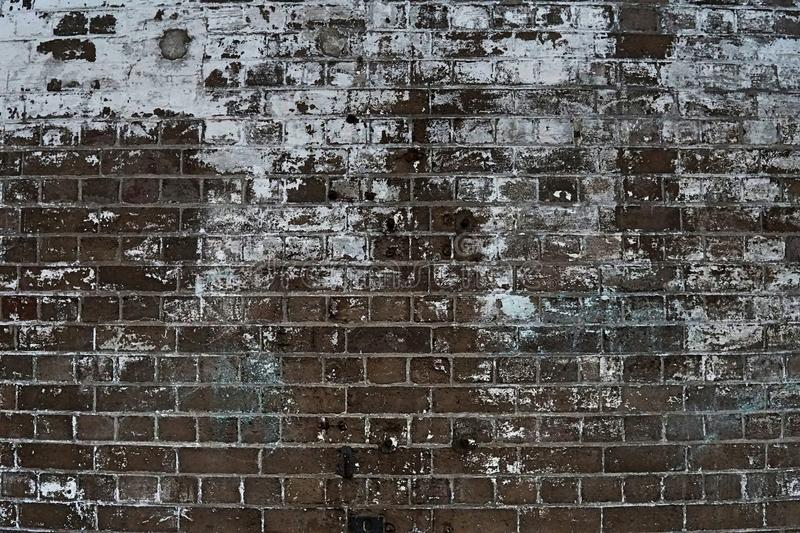 Grain Image of brick stone wall background in detail and texture patte. Rn. Dirty brick wall with peeling paint in abandon factory stock photo
