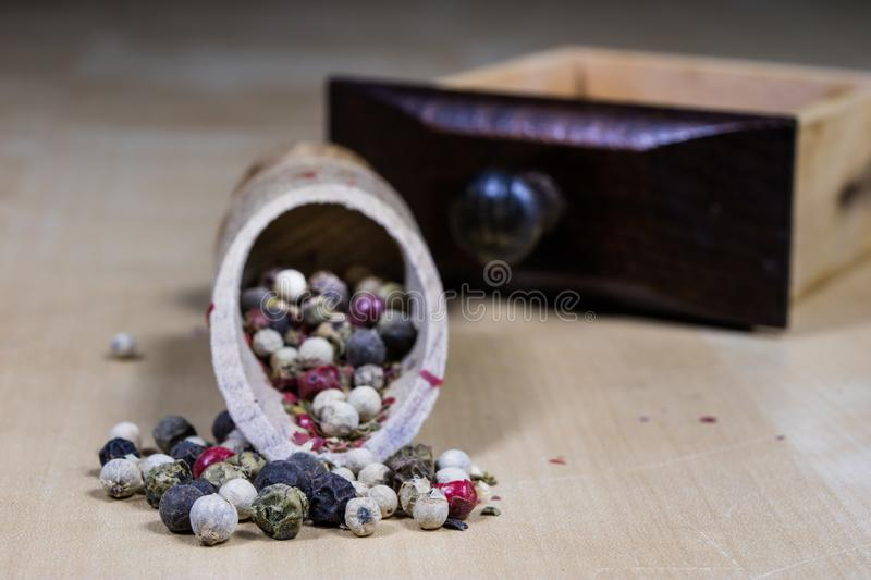 A grain of pepper on a kitchen table. Ground pepper in a kitchen. Mill. Culinary spices on a light background stock image