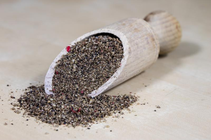 A grain of pepper on a kitchen table. Ground pepper in a kitchen. Mill. Culinary spices on a light background royalty free stock images