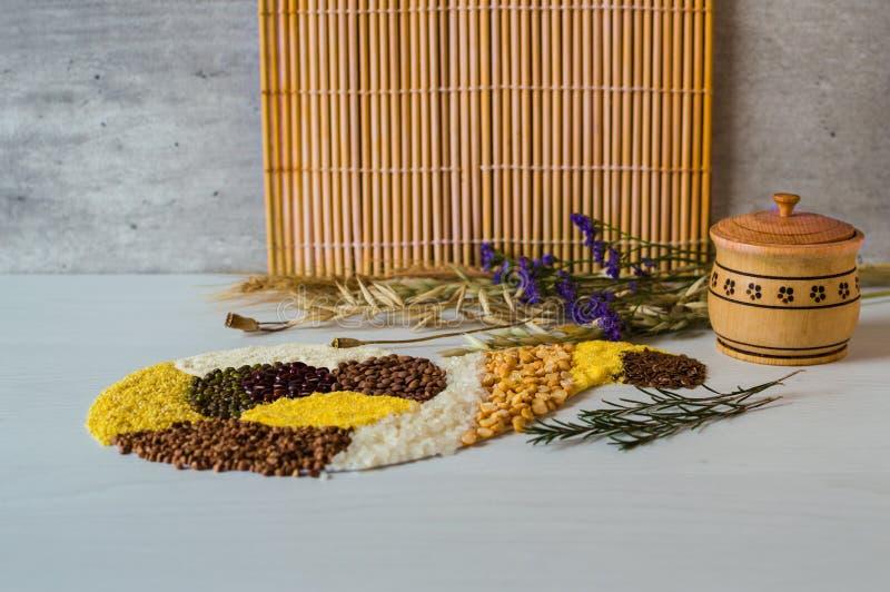 Grain, riz, maïs, pois, semoule et lentille de sarrasin sur un fond en bois blanc sous la forme de klaxon d'abondance photographie stock