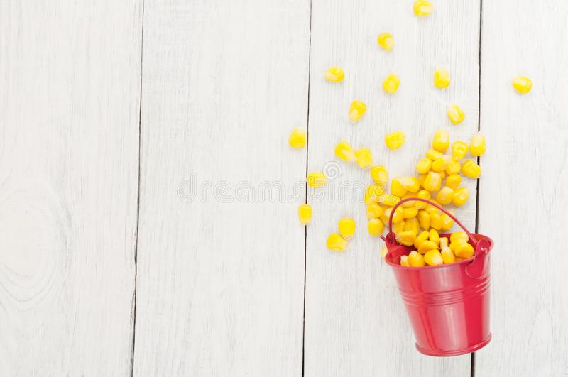 Grain of yellow ripe corn poured out of red metal bucket. On old rural white wooden planks royalty free stock images