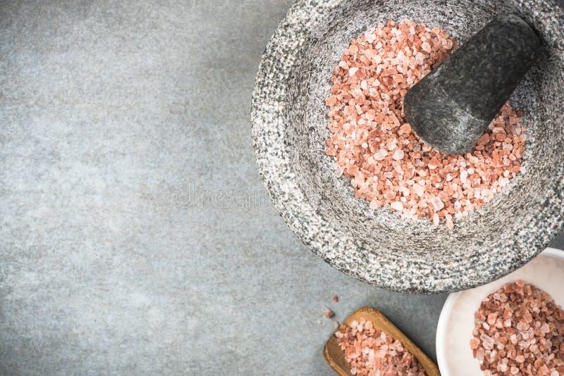 Graine rose de l'Himalaya de sel dans le mortier ou le pilon de granit images stock