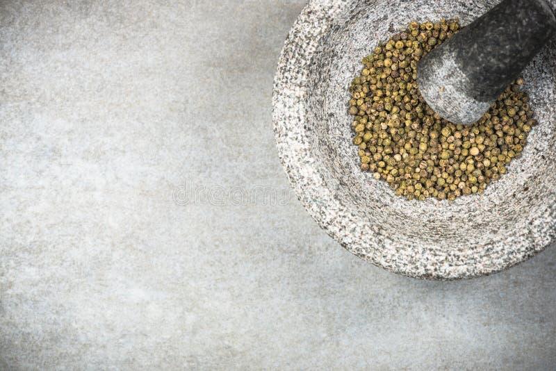 Graine verte de grain de poivre dans le mortier ou le pilon de granit photos stock