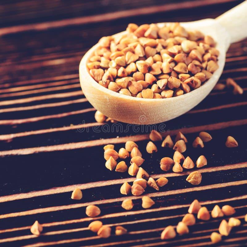 Graines crues de sarrasin dans la cuillère en bois sur la table en bois Eatin sain photographie stock libre de droits