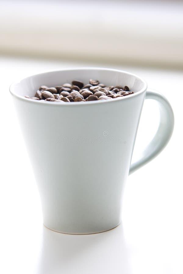 Graines de café entières dans une cuvette photographie stock