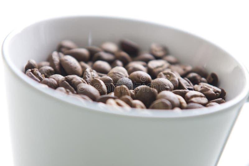 Graines de café entières dans une cuvette de café images stock