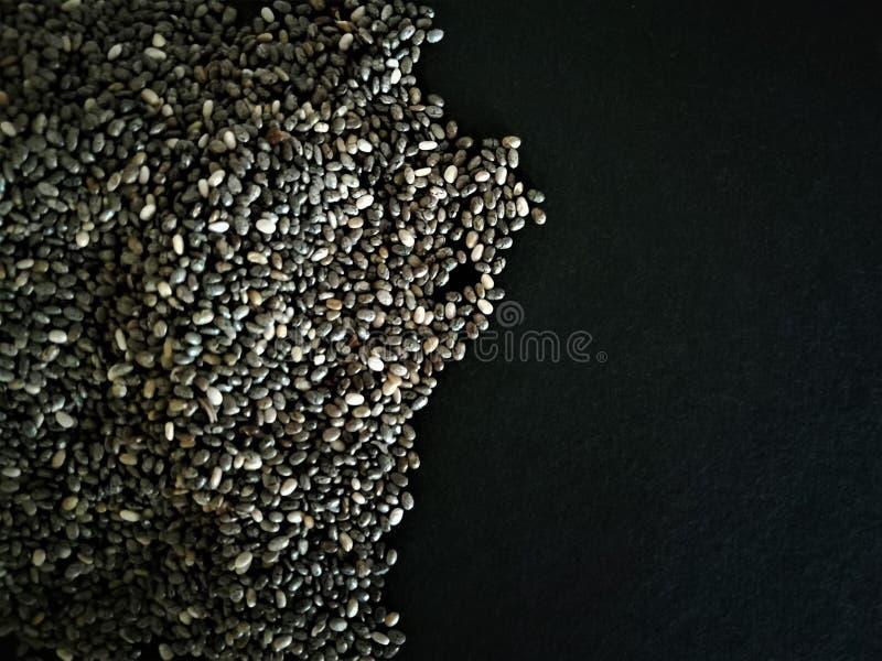 Graines de Chia d'isolement avec le fond noir Nourriture normale images libres de droits