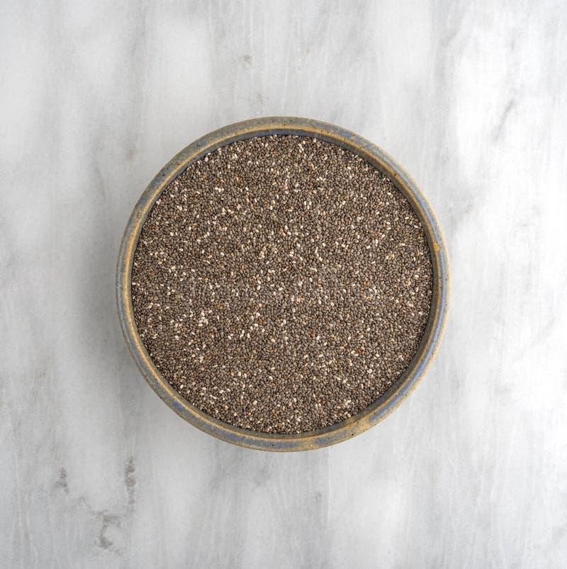 Graines de Chia dans une cuvette sur une planche à découper de marbre photos stock