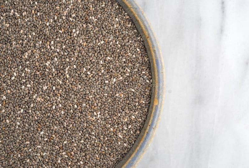 Graines de Chia dans une cuvette sur une planche à découper de marbre image stock
