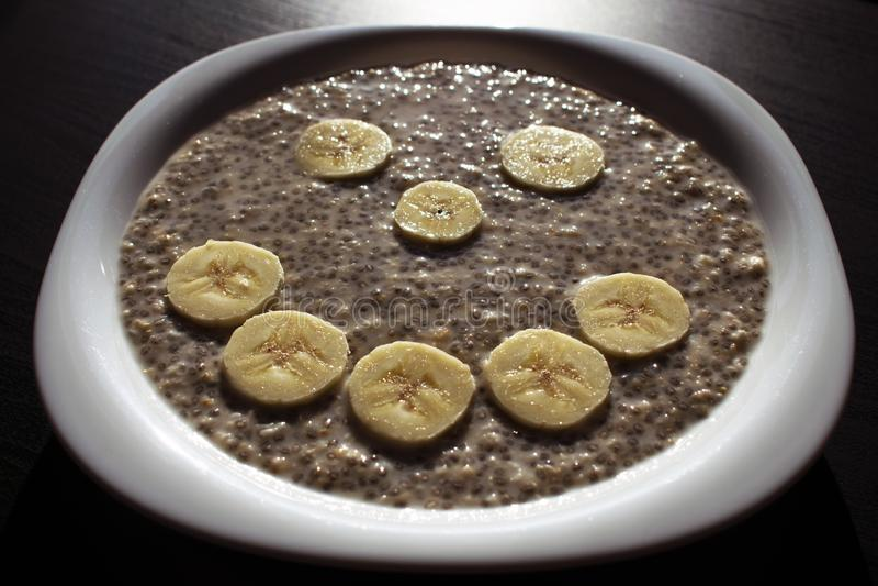 Graines de Chia et flocons d'avoine dans l'eau, avec des tranches de banane disposées dans le visage souriant d'un plat blanc photo stock