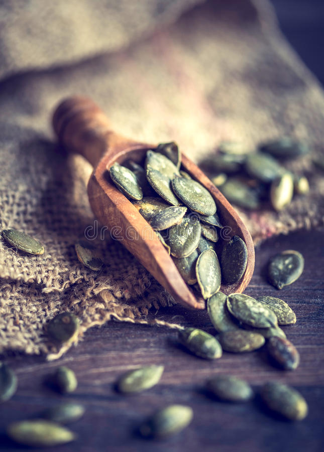 Graines de citrouille dans un scoop en bois image libre de droits