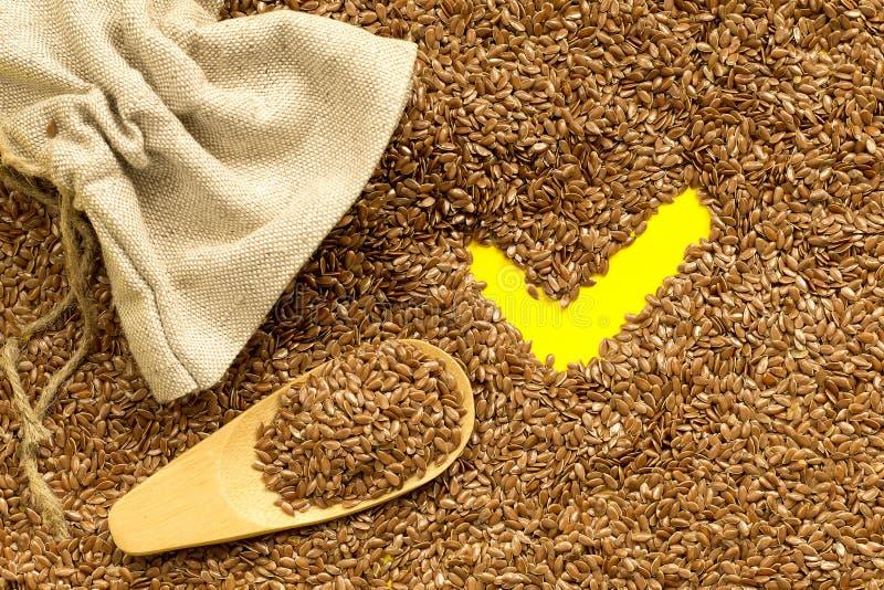 Graines de lin, sac de toile, cuillère en bois et coche jaune image libre de droits