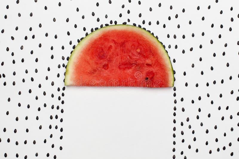 Graines de pastèque pleuvant sur la tranche de melon protégeant la zone dessous comme parapluie image libre de droits