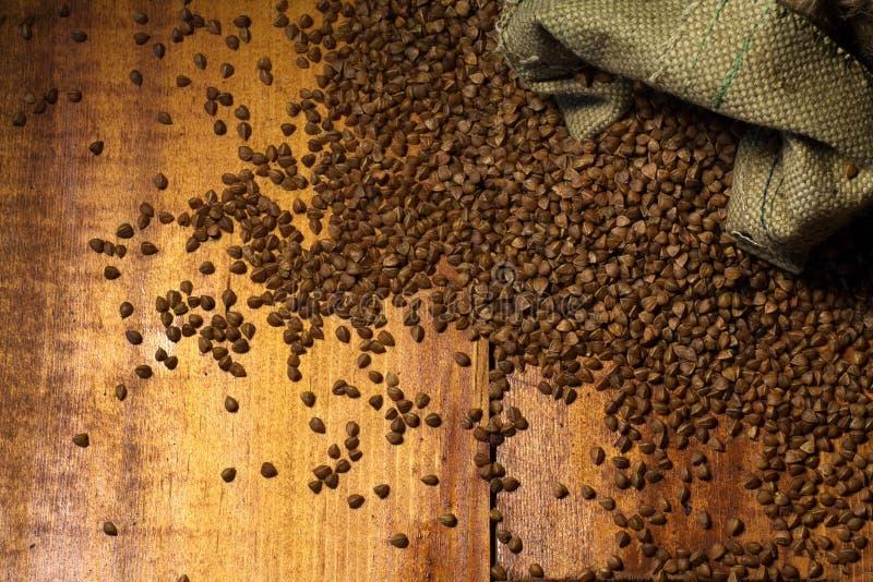 Graines de sarrasin dans la cuillère en bois sur une table en bois brune photographie stock