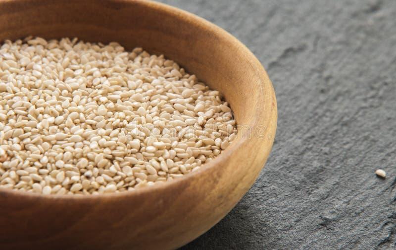 Graines de Sesam dans une lumière naturelle en bois de petite cuvette image libre de droits