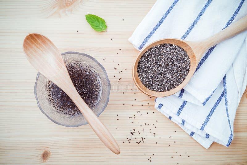 Graines nutritives de chia dans le bol en verre avec la cuillère en bois pour le régime f photos stock