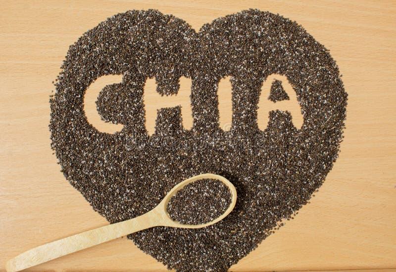 Graines saines de Chia sous forme de coeur Chia dans une cuillère en bois sur un plan rapproché en bois de table image libre de droits