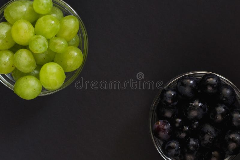 Grains of black and white grape in small glass bowl. Fresh healthy snack. Flat lay, close up stock photos
