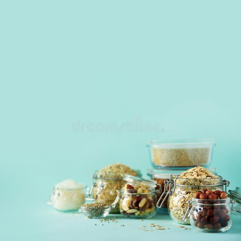 Grains, cereals, nut, dry fruits in glass jars over blue background with copy space. Clean eating, healthy, vegan diet concept royalty free stock photography