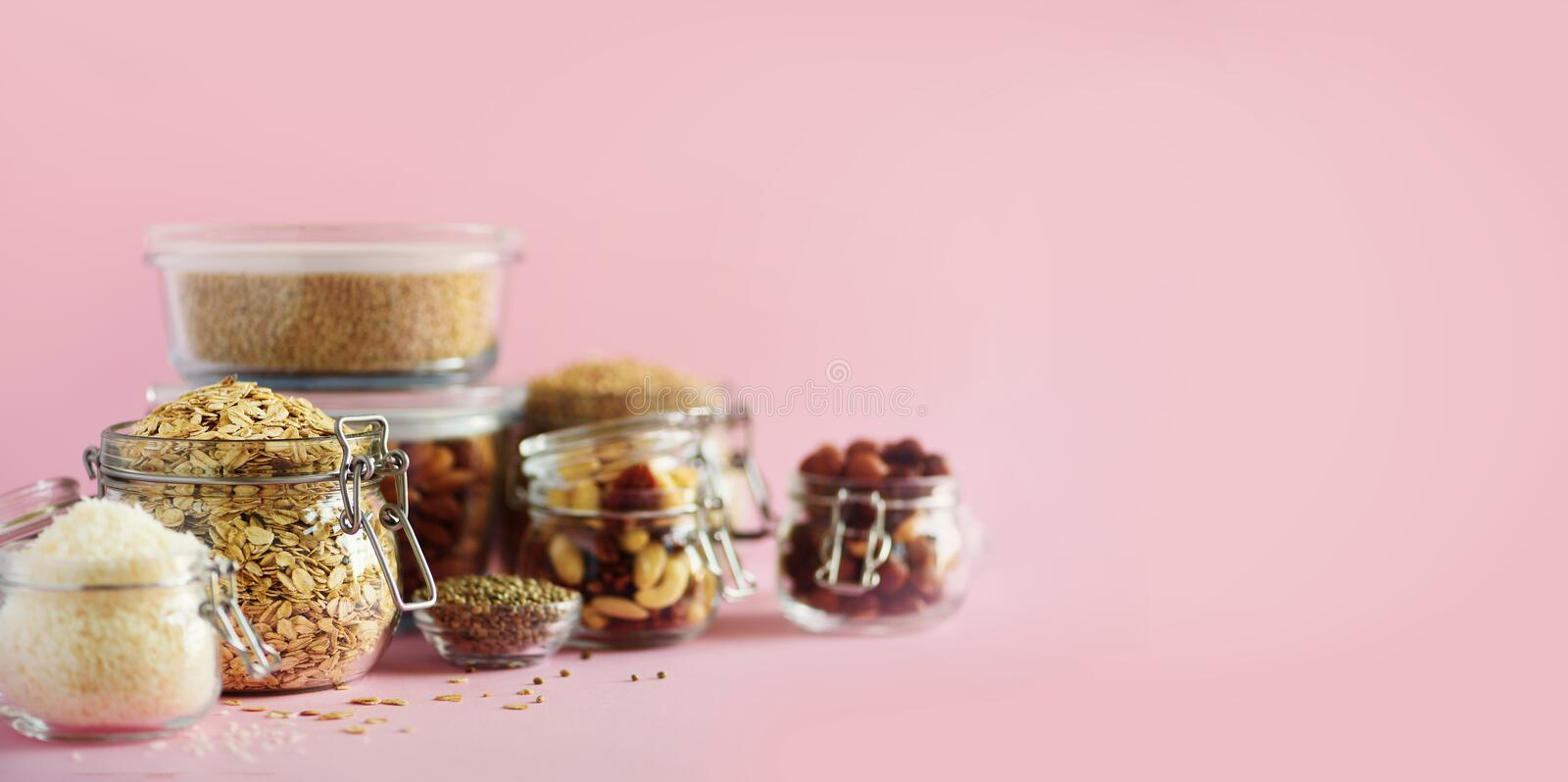 Grains, cereals, nut, dry fruits in glass jars over pink background with copy space. Clean eating, healthy, vegan diet concept.  stock photo