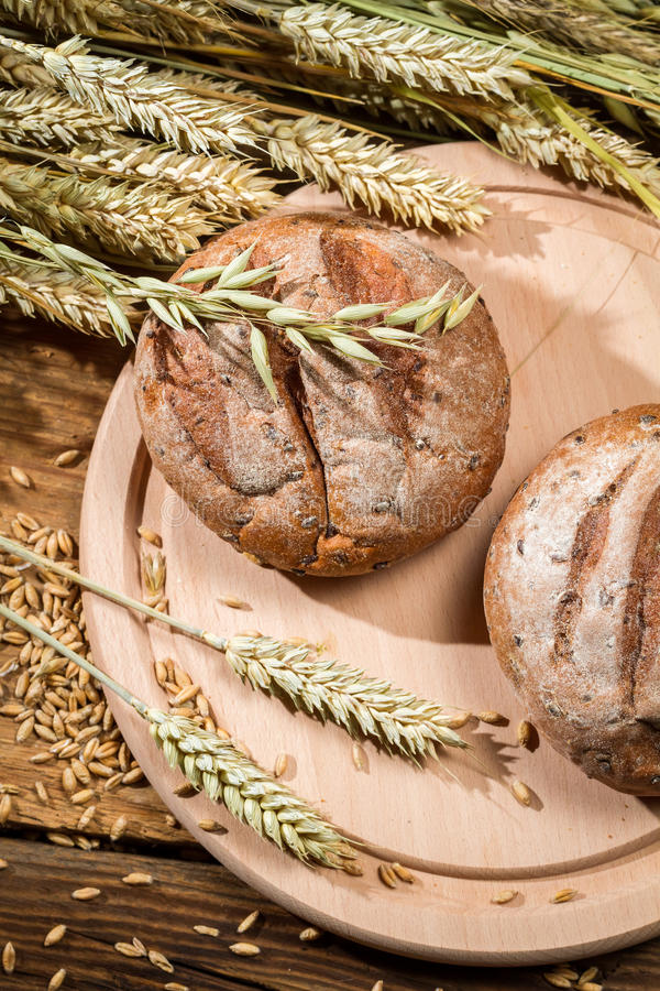 Grains and cereals on a wooden board with bread rolls royalty free stock photo
