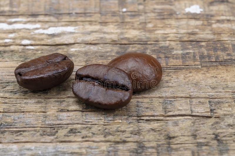 Grains of coffee on an old wooden surface. Fragrant roasted brown coffee tree grains. Close-up royalty free stock photos