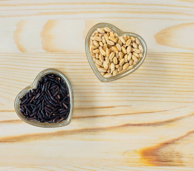 Grains de blé et riceberry entiers dans la cuvette en forme de coeur en verre image libre de droits