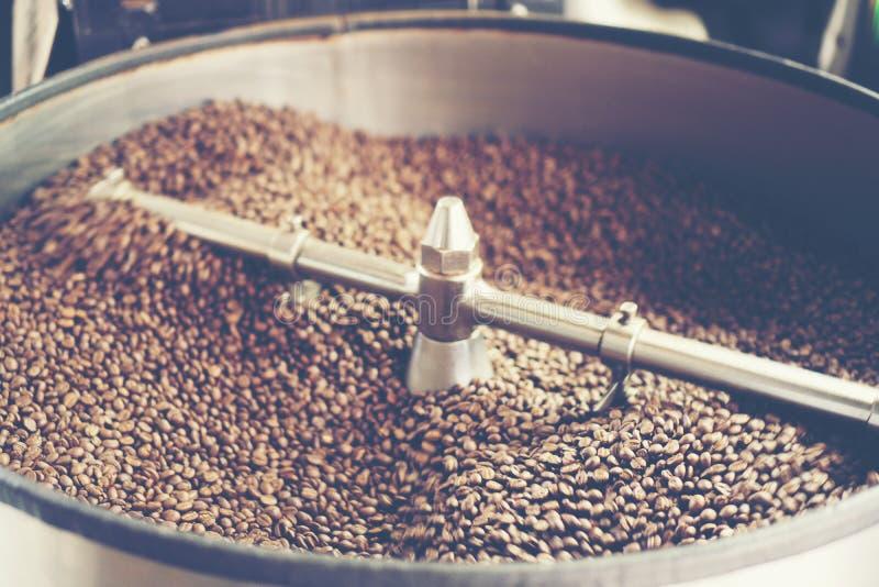 Grains de café aromatiques fraîchement rôtis dans un roastin moderne de café image stock
