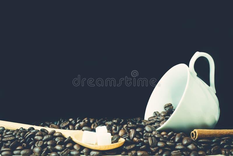 Grains de café avec la cuillère en bois, cube en sucre, bâtons de cannelle et images stock