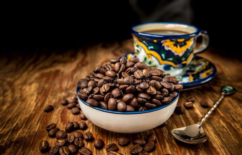 Grains de café avec la tasse et soucoupe photos stock