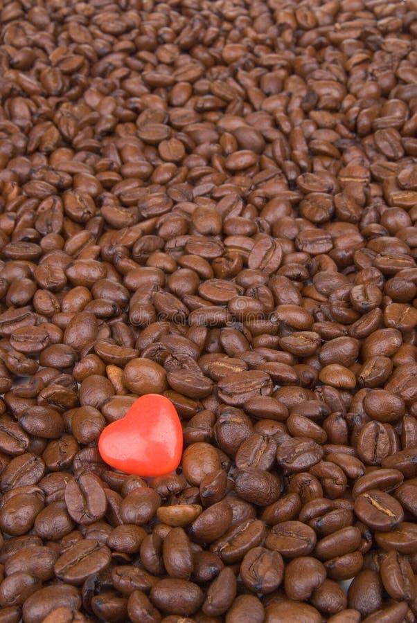 Grains de café avec un coeur rouge de valentine photos stock