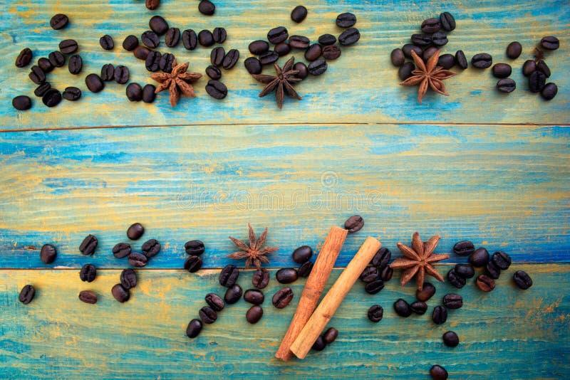 Grains de café, bâtons de cannelle et anis d'étoile sur le fond en bois image libre de droits