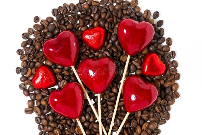 grains de café, bonbons au chocolat et coeurs décoratifs sur des bâtons image stock
