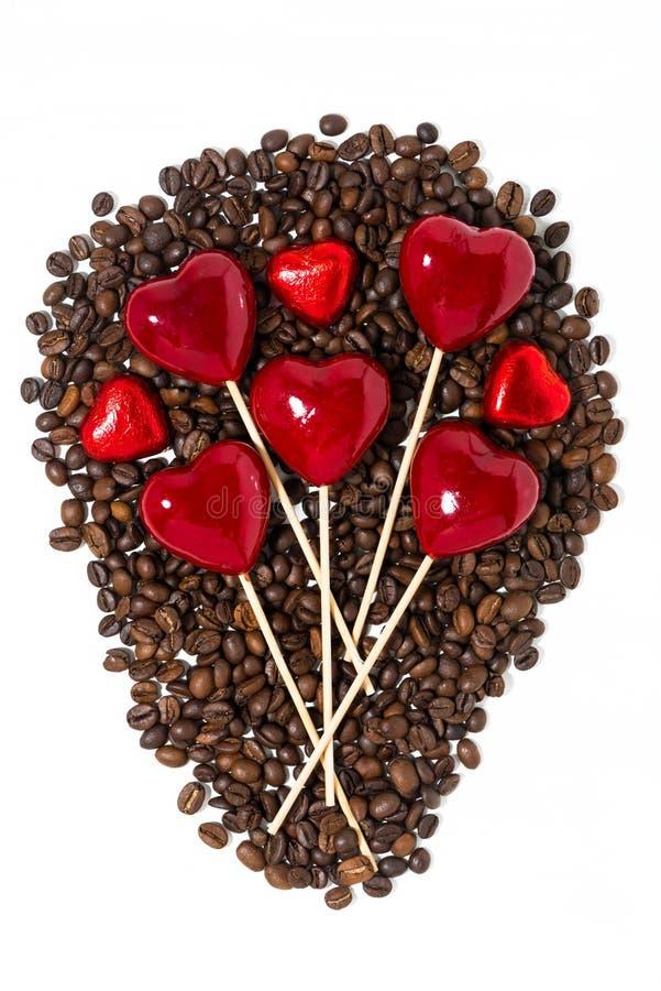 grains de café, bonbons au chocolat et coeurs décoratifs sur des bâtons images stock