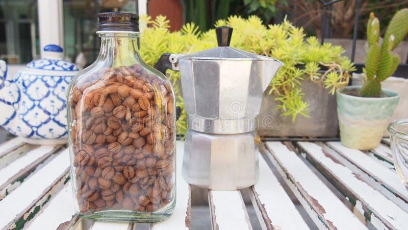 Grains de café dans la bouteille en verre avec le pot de thé de bouilloire et de céramique sur la table en bois images stock