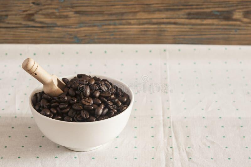 Grains de café dans la cuvette en céramique blanche sur la table photo stock