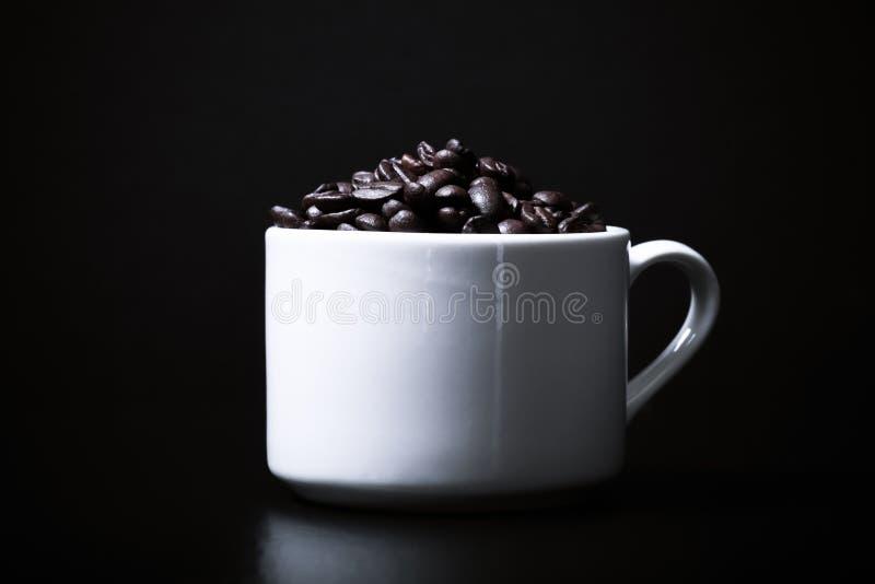 Grains de café dans la tasse sur le fond noir toned photographie stock